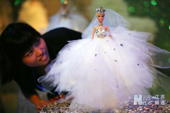 8月11日,在南京网友婚博会上,一婚庆服务企业展位上的婚纱模特吸引了市民目光。