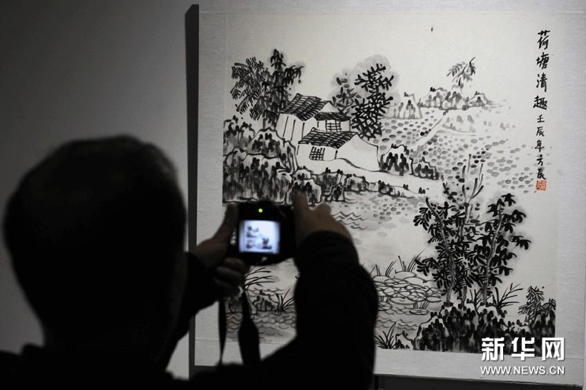 观众在拍摄展出的水墨艺术作品