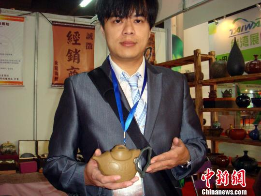 """10日上午,第三届中国茶都安溪国际茶业博览会在福建安溪县隆重开幕,图为一参展台湾客商在展示其设计生产的创意茶具""""两岸交流壶"""",该壶壶身酷似中国地图。郭斌摄"""