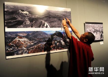 一名从西藏来的参观者用手机拍摄自己喜欢的摄影作品。新华网图片 罗晓光摄