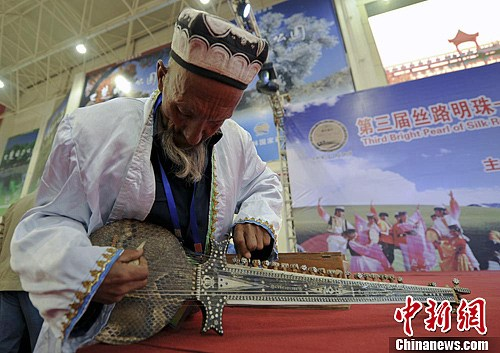 图为展馆现场,一位老人正在调试自己的乐器。刘新 摄