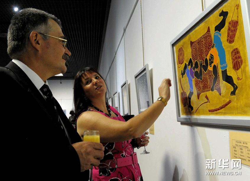 11月20日,观众在南非比勒陀利亚迪宗国家文化史博物馆观赏中国农民画。