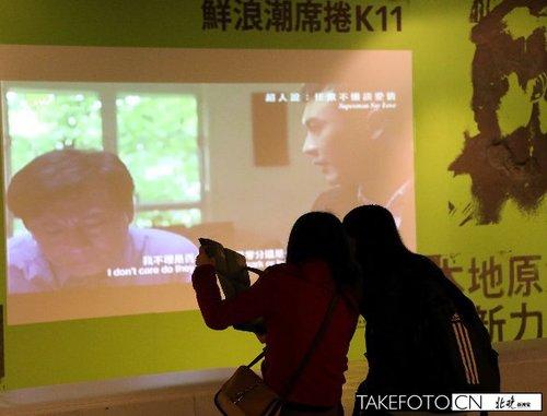 12月1日,两位观众在香港K11观看正在这里举行的鲜浪潮2012国际短片展。