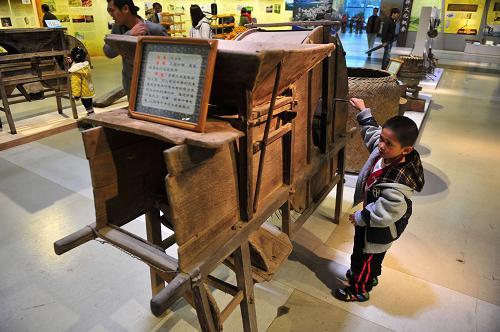 12月1日,一位小朋友在体验广西传统农具——风谷机。