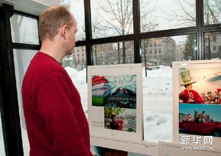 """12月22日,参观者在瑞典斯德哥尔摩国王花园影廊欣赏""""大美新疆""""摄影展图片。新华网图片 刘一楠 摄"""