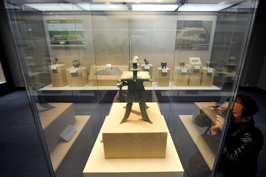 12月25日,一位参观者在拍摄河南省安阳市殷墟郭家庄160号墓出土的铜方斝。