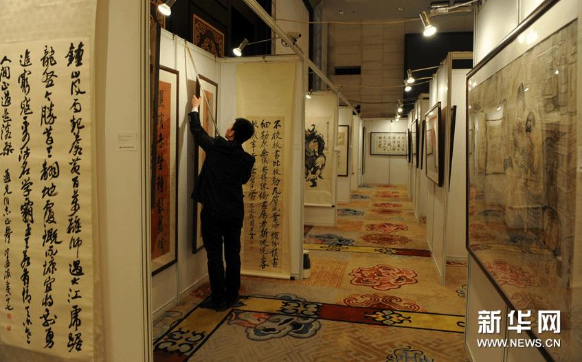 1月24日,一名工作人员在呼和浩特首届文物艺术品拍卖会预展现场悬挂展品。