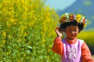 罗平头戴油菜花环的小童。(黎旭阳摄)