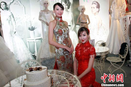 """2月15日,香港靓丽模特在""""第70届情人节婚纱、婚宴及结婚服务博览""""上展示婚纱。一连3天的展览汇聚超过800个婚嫁服务商家,包括婚纱摄影、婚宴酒席、珠宝钻饰、化妆造型、海外婚礼、蜜月旅游、中西礼饼、名贵红酒等过万种产品服务,为准新人轻松筹备婚礼提供丰富选择平台。中新社发 洪少葵 摄"""