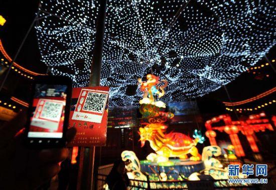 2月6日,市民在南京夫子庙里的大型灯组前用手机刷二维码,获取祝福语。