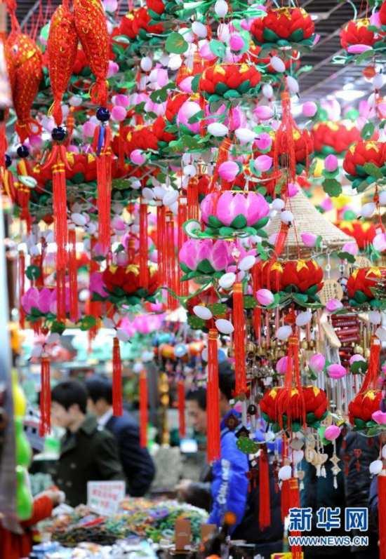 2月6日,游人在南京夫子庙街区的一家商店里参观选购秦淮花灯等工艺品。