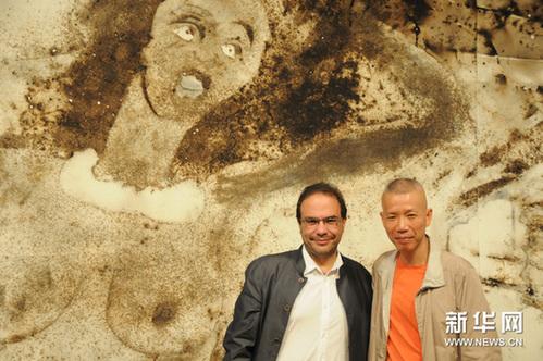 2月4日,在巴西城市巴西利亚举行的《农民达芬奇》展览上,蔡国强(右)和巴西策展人马塞罗•丹塔斯在用火药爆炸绘制的表现巴西狂欢节的大型画作前合影。新华网图片 刘彤 摄