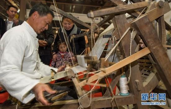"""2月28日,中国非物质文化遗产""""荣昌夏布""""折传承人在现场为市民展示织布工艺。"""