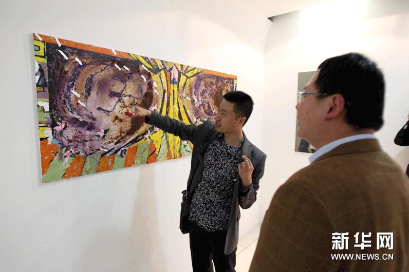 阿尔及利亚首都阿尔及尔举行的中国画家采风作品展上,来自黑龙江的青年画家杨广文向参观者讲解画作。