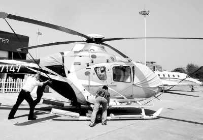 4月16日,2013亚洲商务航空展在上海虹桥机场公务机基地开幕,此次航空展吸引了波音、空客、庞巴迪等180家参展商参展。图为工作人员对参展飞机进行最后调整。新华社记者  陈  飞摄