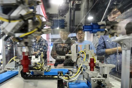 4月18日,观众在电子信息博览会上观摩智能机器的工作流程。新华社发(李忠 摄)