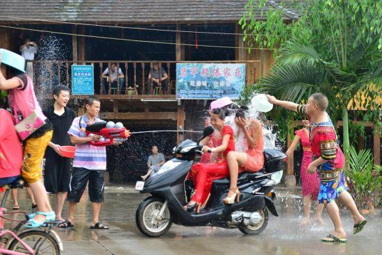 傣族园寨内村民和游客祝福泼水