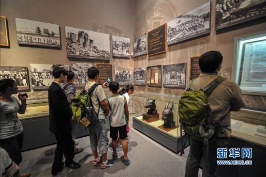 7月18日,游客在鼠首兔首前参观拍照。