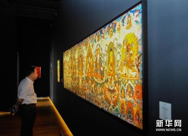 观众在欣赏由娘本绘制的彩唐《莲花生大师八变》