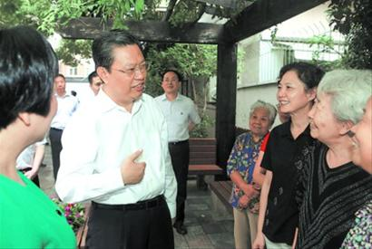 中共中央政治局委员、中央组织部部长赵乐际在上海长宁区虹储居民区与群众交流。刘歆 摄
