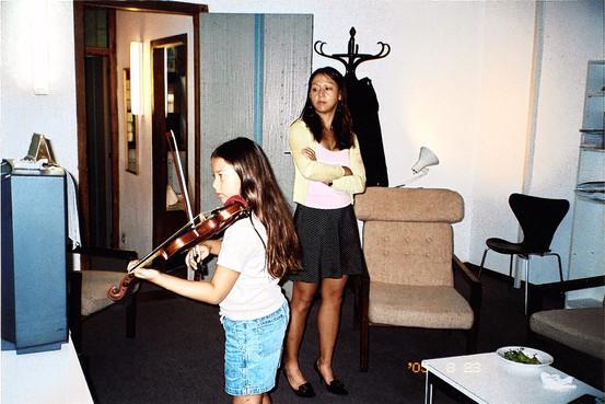 蔡美儿督促女儿在关闭的电视前练小提琴。(《华尔街日报》图片)
