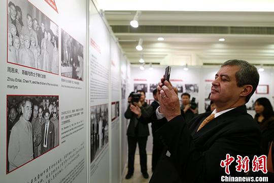 图为阿尔及利亚驻中国大使哈桑纳•拉贝希用手机拍摄展板上周恩来总理的照片。中新社发 富田 摄