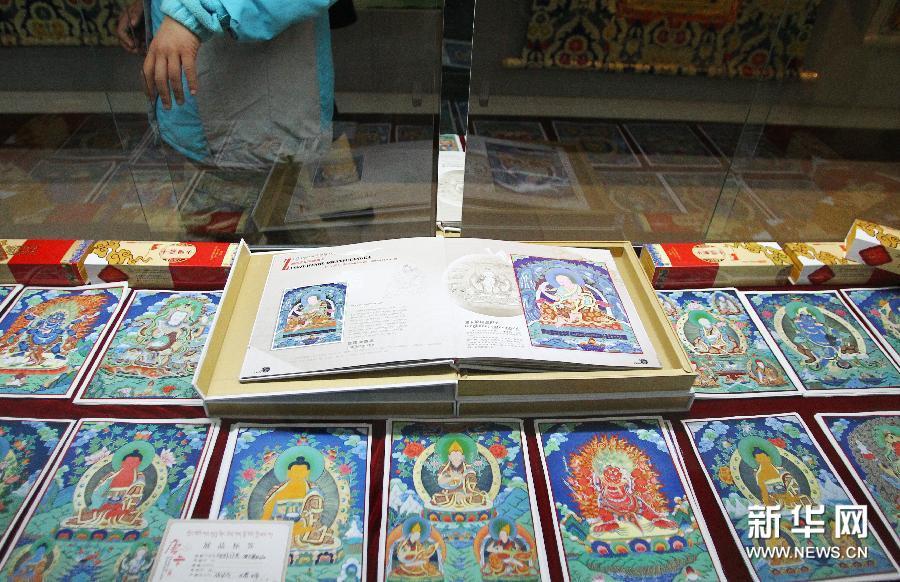 (3)1月16日,在韩国首尔中国文化中心,参观者观赏介绍唐卡作品的图册。