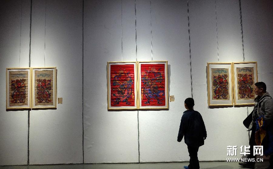 (3)1月28日,参观者在观看传统年画。
