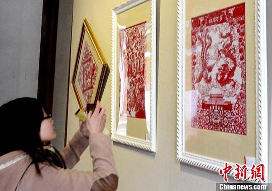 """2月10日,中国农历元宵节临近。正在福建省海峡民间艺术馆举行的""""剪春风——闽台剪纸艺术展""""上,50余件福建民间剪纸作品和20余件台湾立体剪纸作品,以其巧妙的构思与创意,将传统与现代相结合,呈现出了鲜明的民族特色。吸引众人观展。中新社发 刘可耕 摄"""