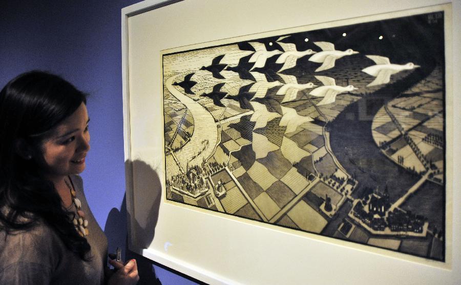 (1)2月26日,一名参观者在台北故宫图书文献大楼欣赏荷兰艺术家艾雪的石版画《三个世界》。