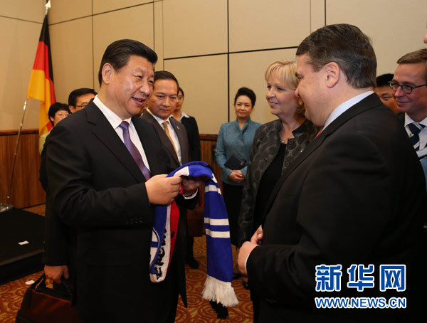 3月29日,中国国家主席习近平在杜塞尔多夫出席中德工商界举行的招待会并发表题为《把握中国机遇,实现共同发展》的重要讲话。这是招待会开始前,习近平在会见中德企业家代表时,德国副总理兼经济和能源部长加布里尔(前右)向习近平赠送一家德国足球俱乐部球迷标志性围巾。新华社记者 刘卫兵 摄