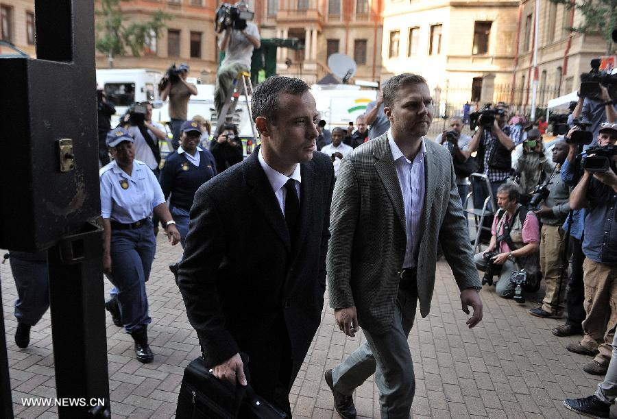 South African Paralympic athlete Oscar Pistorius (L), charged with murder of his girlfriend Reeva Steenkamp, walks to Pretoria