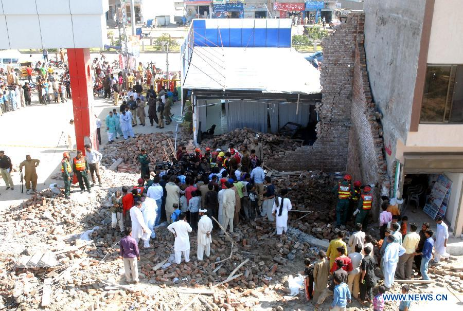 Rescuers search for victims and survivors at the collapsed building in eastern Pakistan