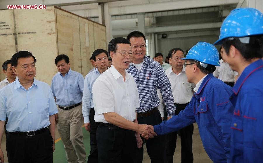 Chinese Vice Premier Zhang Gaoli (C), also a member of the Standing Committee of the Political Bureau of the Communist Party of China Central Committee, visits Lanzhou Haimo Technologies Co. Ltd. in Lanzhou, capital of northwest China