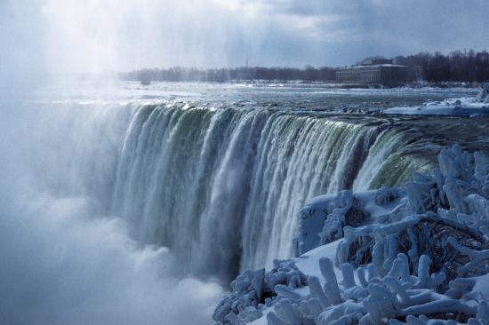 """尼亚加拉大瀑布   清晨,从纽约出发,驱车前往被称作""""水牛城""""的布法罗,目的是看心仪已久的尼亚加拉大瀑布。   应该说,这实在不是看大瀑布的季节,阴霾的冬日,雪花飘飘,气温已在零下10摄氏度左右,瀑布会不会冰封?心里没底。但是10年前与之失之交臂,这次是无论如何要了却心愿的。   从纽约到布法罗要八九个小时的车程,雨雪天车难开,时间更长,一路上是既顺又不顺。顺的是仅管道路两旁都是厚厚的积雪,天上还在纷纷扬扬地下着雪,但路中间没一点积雪,畅行无阻。不顺的是竟两次因超速被警察逮着,一"""