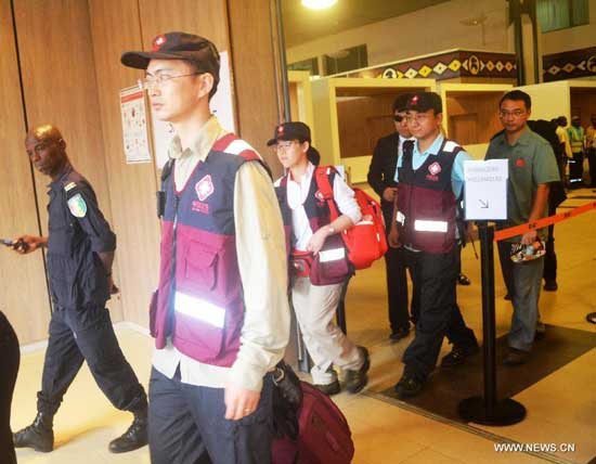 Three Chinese disease control experts arrive at the airport of Conakry, capital of Guinea, Aug. 11, 2014. The National Health and Family Planning Commission (NHFPC) announced on Saturday that China would send three expert teams and medical supplies to Guinea, Liberia and Sierra Leone to assist the prevention and control of the Ebola virus. (Xinhua/Cellou)