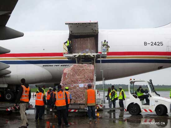 Local workers unload emergency humanitarian supplies provided by China from a chartered plane at the airport in Freetown, capital of Sierra Leone, Aug. 11, 2014. A Chinese plane carrying emergency humanitarian supplies for Sierra Leone arrived in the country