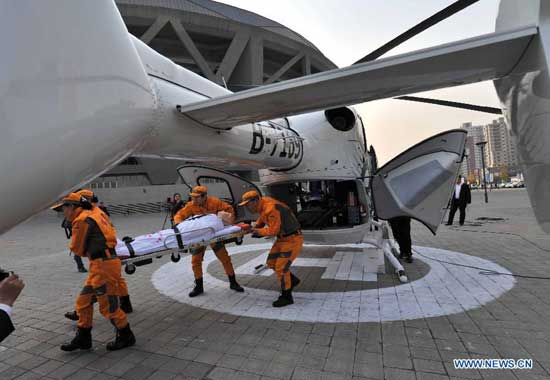 Air rescue team members take part in a drill in Beijing, capital of China, Oct. 28, 2014. The ambulance helicopter, an EC135 aircraft equipped with aerial medical devices, will serve the professional air rescue team of the Beijing Red Cross Foundation. (Xinhua/Li Wen)