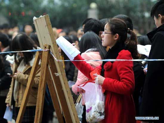 A candidate checks her information at Anhui University of Chinese Medicine exam site in Hefei, capital of east China