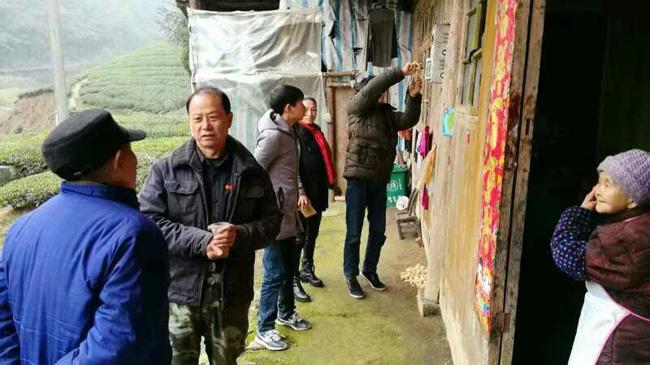 王新法(左二)生前走访薛家村群众,共商脱贫大计。