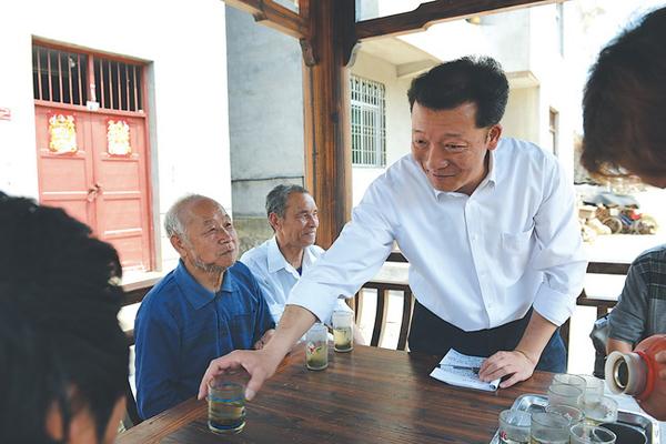 2014年4月18日,廖俊波(右一)在铁山东涧村调研,与村民座谈,给老人递上茶水。 徐庭盛 图