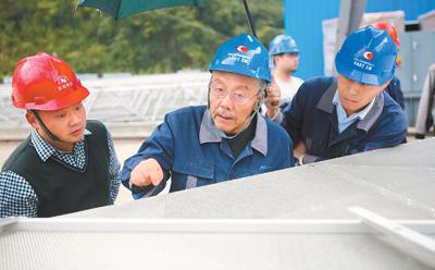 南仁东(左二)在贵州大窝凼施工现场指导反射面单元拼装工作(2019-02-21摄)。