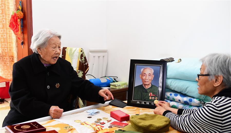 娄淑珍(左)与女儿一起整理周智夫获得的荣誉章(2018年4月8日摄)。