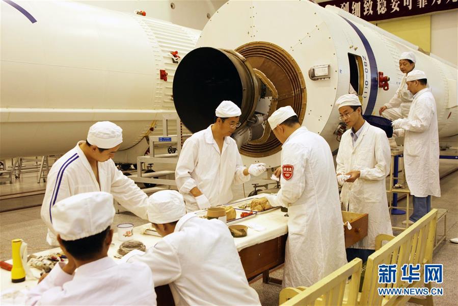 在西昌卫星发射中心总装车间,科研人员正在安装火工品(2009年8月11日摄)。新华社发(航天科技集团第一研究院供图)