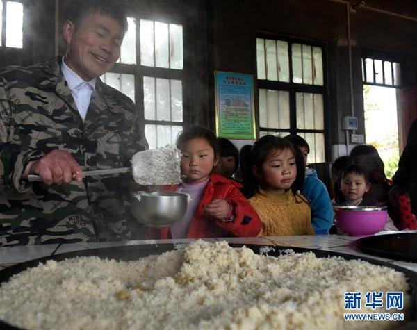 张玉滚在为学生们盛午饭(3月20日摄)。新华社记者 李嘉南 摄