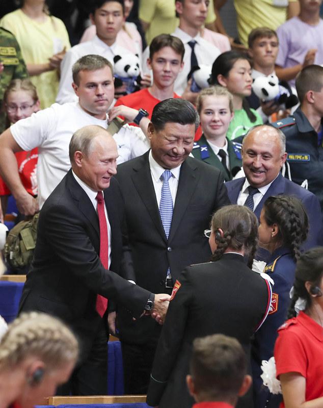 """9月12日,国家主席习近平在符拉迪沃斯托克同俄罗斯总统普京一起访问""""海洋""""全俄儿童中心。这是习近平和普京在""""海洋""""全俄儿童中心接待汶川地震灾区儿童10周年纪念仪式上同孩子们亲切交谈。新华社记者 谢环驰 摄"""
