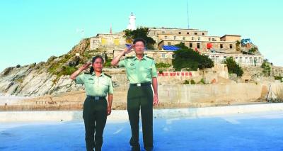 图为王继才生前和爱人王仕花向离岛的人们敬礼送别。吴晨光摄 光明图片/视觉中国