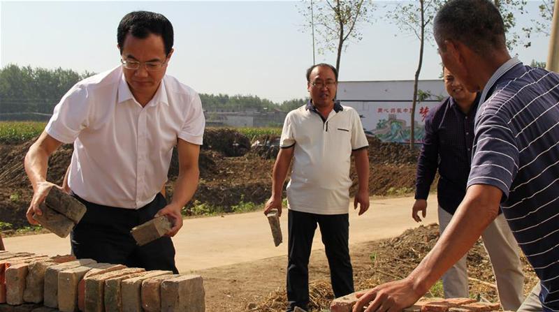 邓真晓(左一)在临泉县艾亭镇枣树庄村与村民一起进行环境整治工作(9月8日摄)。新华社发