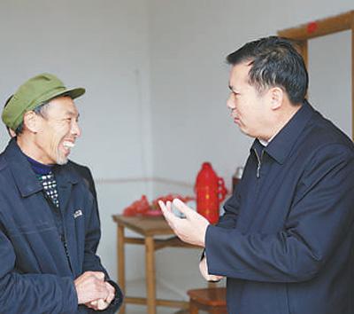 刘洪(右)在下七乡下七村走访贫困户。(资料照片))