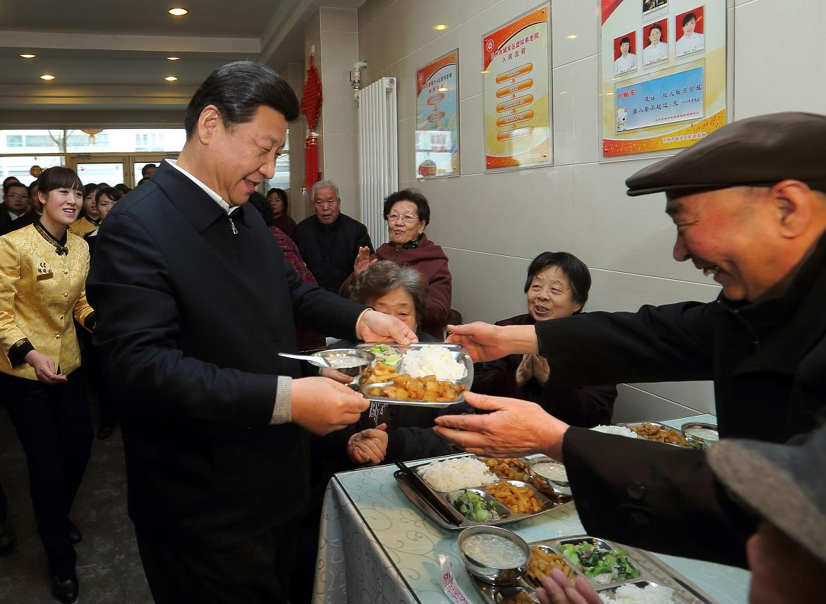 """2013年2月4日,习近平来到兰州一家""""虚拟养老院""""的养老餐厅,了解有关情况,还端起一个盛满饭菜的餐盘,走到72岁的老人杨林太面前,轻轻送上,请他用餐。"""